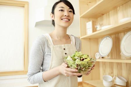 Femme au foyer portant des légumes Banque d'images