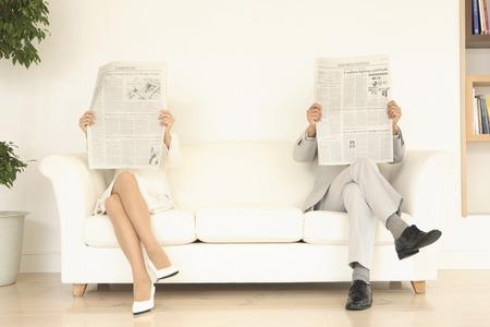 ソファの両端で新聞を読み女性および人