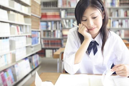 ライブラリのブックを開くに女子高校生 写真素材
