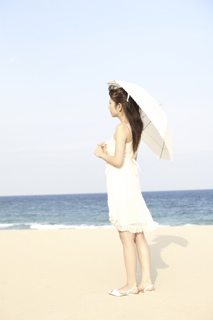 one piece dress: Woman holding an umbrella on the beach