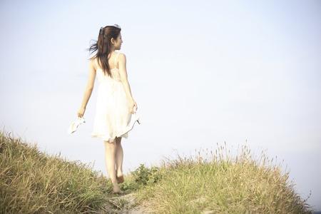 裸足で歩く女性の後姿 写真素材
