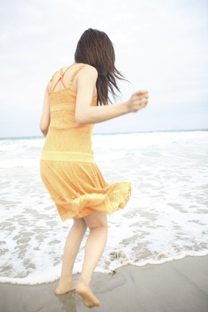 one piece dress: Rear View of a woman standing on the beach