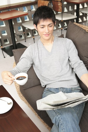 young fellow: Men read a newspaper coffee in one hand Stock Photo