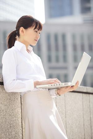Career woman operating a personal computer Banco de Imagens