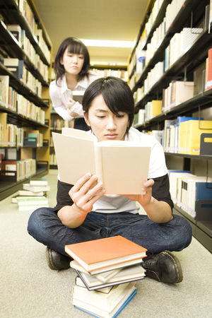 plural number: Students read a book and sitting down Stock Photo