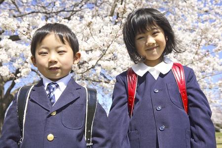 초등학교 남성과 여성은 벚꽃의 앞에 서