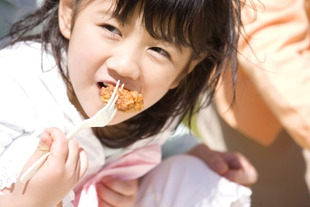 three generations of women: Girl eating fried from