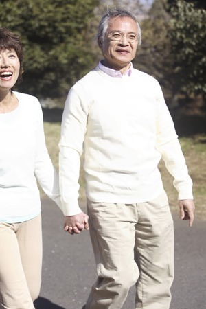 2 50: Senior couple walking in the park hand in hand