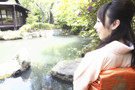 lean over: Kimono woman overlooking the pond Stock Photo