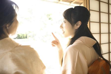 Two kimono women sit on the veranda Stock Photo