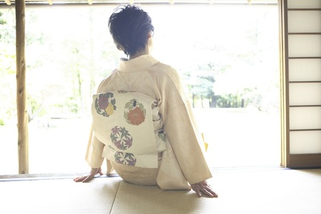 From behind the kimono woman standing on the veranda