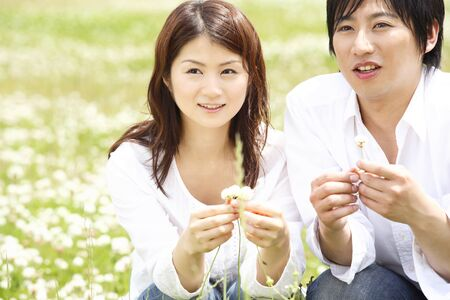 japanese people: Couples pluck the white claws grass in the park