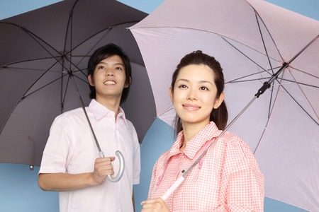 refers: Men and women, which refers to the umbrella Stock Photo