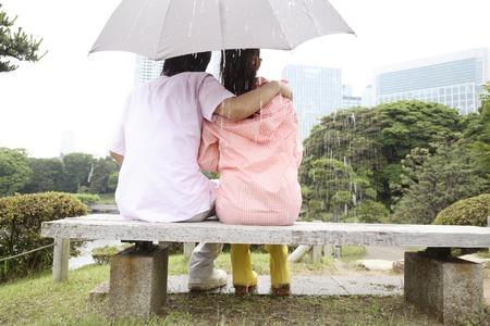 背面ベンチに傘座っているのカップルの