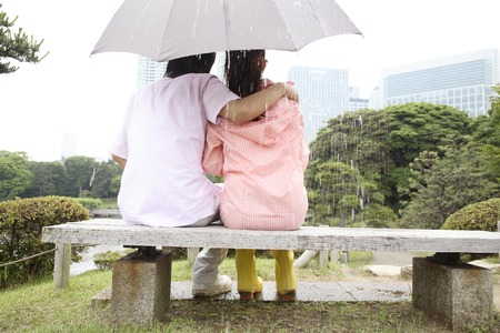 rain japan: Rear View of couple you are an umbrella sit on the bench