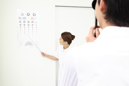 examen de la vista: Enfermera que ver con los hombres que se someten a un examen de la vista