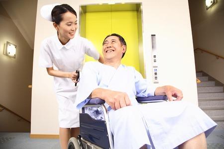 Nurse pushing a patient riding in a wheelchair 免版税图像