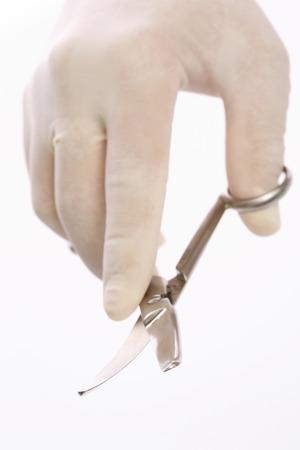 utiles de aseo personal: Mano de un médico con tijeras Foto de archivo