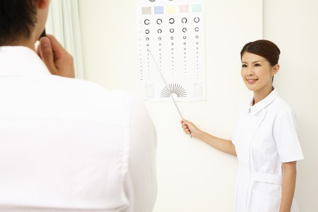 prueba de vision: Enfermera que ver con los hombres que se someten a un examen de la vista