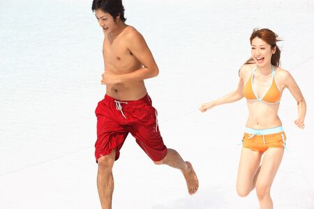 hombres corriendo: Swimsuit couple that runs the waterside Foto de archivo