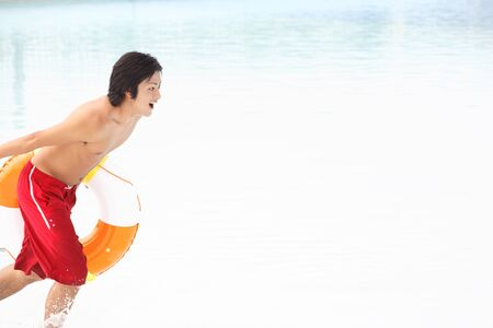 inner tube: Men run the waterside with a inner tube
