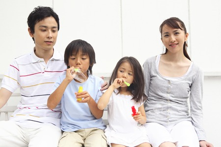 plural number: Family playing with soap bubble Stock Photo