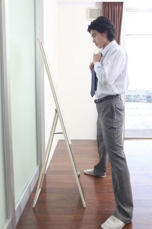 男性は、鏡で見ながらネクタイを締めます 写真素材