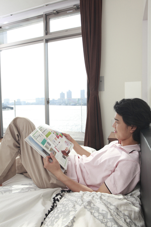 young fellow: Men see the magazine lying down in bed Stock Photo
