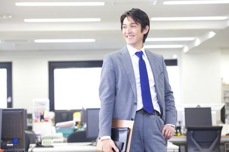Zakenman wandelen in het kantoor met een notebook Stockfoto