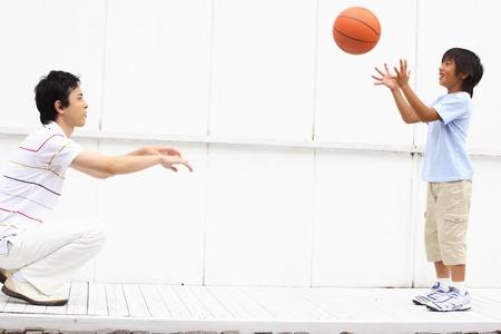 niÑos contentos: Padre e hijo que tienen una pelota de baloncesto