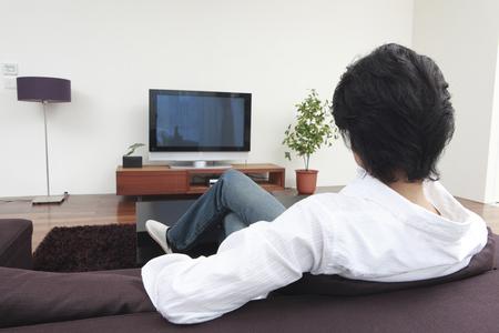 seres vivos: Parte trasera de los hombres que ven televisión en la sala de estar