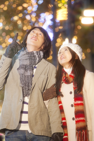 christmas illuminations: Couples walk while watching the Christmas illuminations Stock Photo