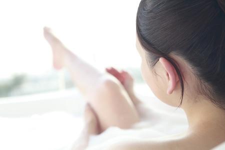 Les femmes se frottent les jambes dans le bain Banque d'images