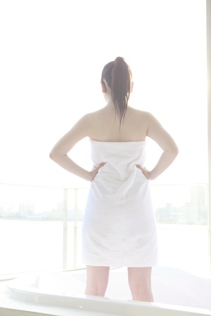 bath: Back view of woman standing by winding a bath towel on the body