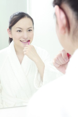 oriental bathrobe: Woman that the toothpaste in the wash basin Stock Photo