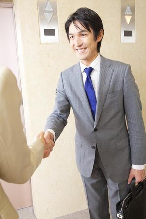 ビジネスマンや OL、廊下で握手
