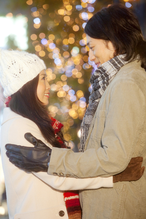 christmas illuminations: Couples each other staring into Christmas illuminations back