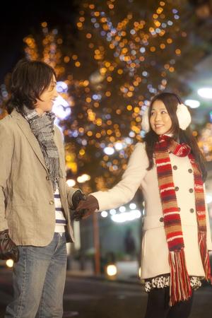 christmas illuminations: Couples walk the streets that was decorated for Christmas illuminations