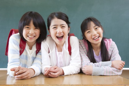 Elementary school girls three people to smile in front of a blackboard Banque d'images