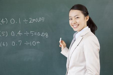 女性教師が黒板に問題を書いて