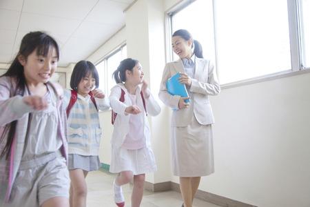廊下を歩く小学生女の子はしゃぐと女性教師
