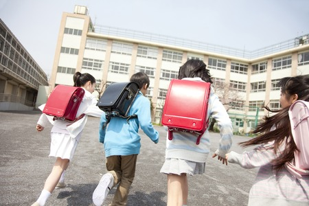 school friends: Rear View of four elementary school students to school Stock Photo