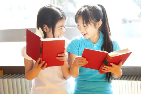 Elementary school girls reading books in the library
