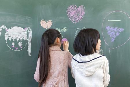 Elementary school girls draw pictures on the Blackboard