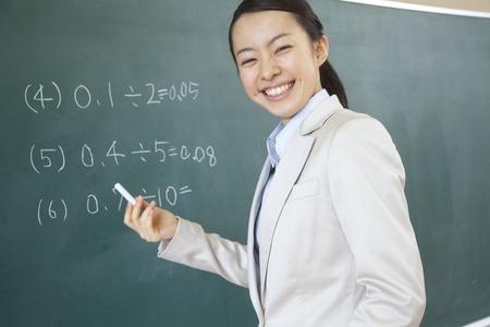 黒板に問題を書く女性教師