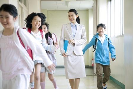 Elementary school students men and women frolic with women teachers walk the hallway