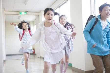 Elementary school students men and women running down the hallway