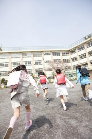 Rückansicht von vier Grundschüler zur Schule
