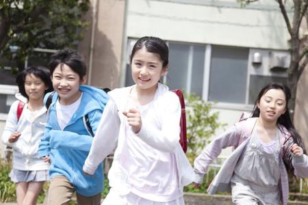 4 つの小学生が学校から帰宅します。 写真素材