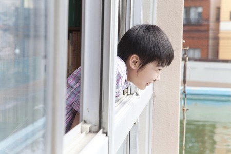 classwork: Elementary school children look out from the window of the library male Stock Photo